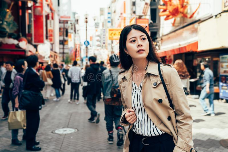 Asian woman standing on the busy urban street stock images
