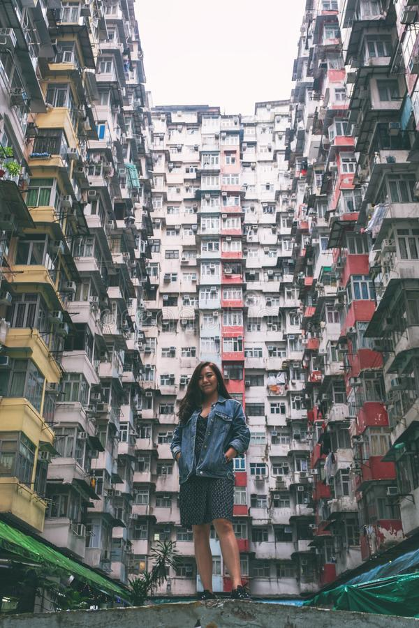 Asian woman standing among the crowded residential building of the community in Quarry Bay, Hong Kong royalty free stock photo