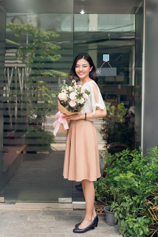 Asian woman standing in flower shop and holding bouquet of flowers royalty free stock photos