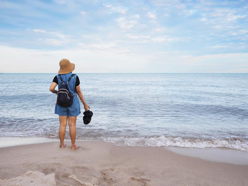 Asian woman standing relaxedly alone on sand along the beach in the morning royalty free stock photos