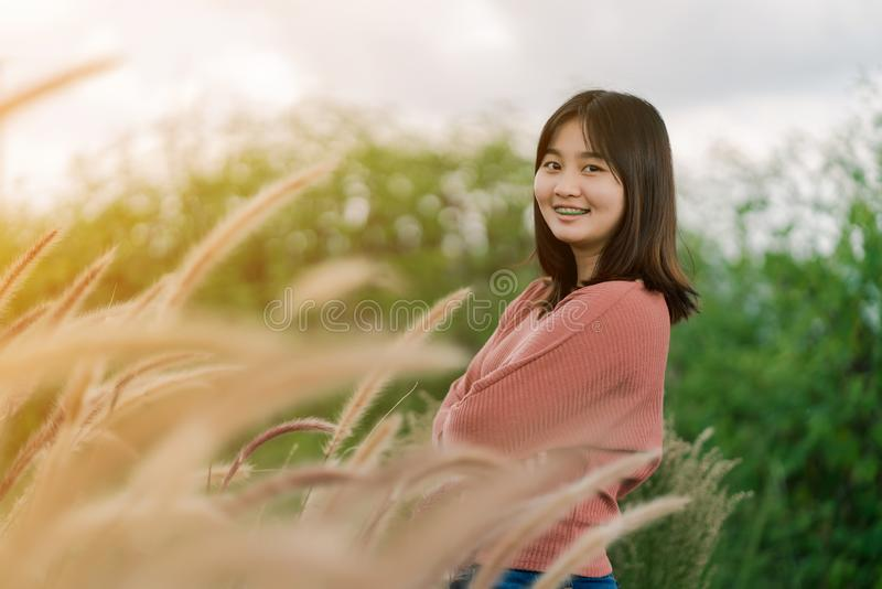 Asian woman Standing smiling in the fields of brown grass in the morning sun With a happy face.  stock photos