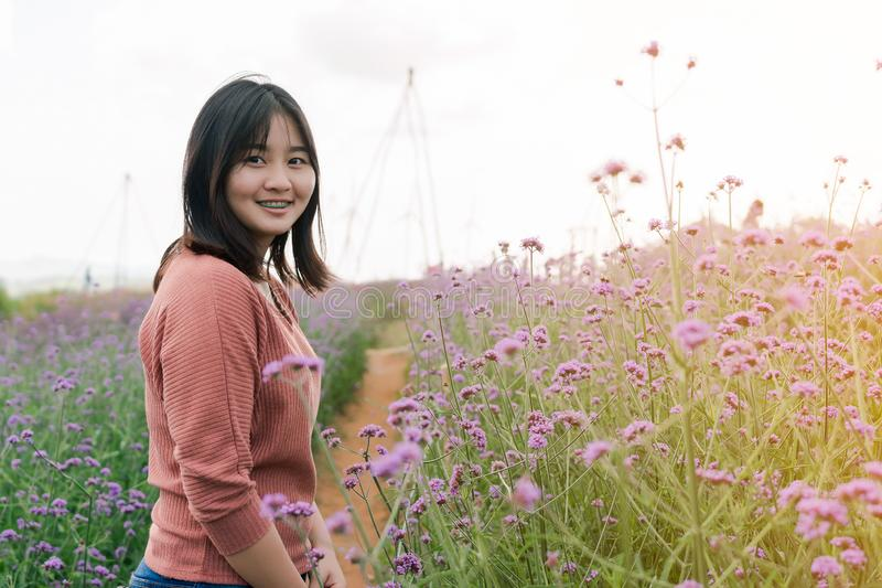 Asian woman Standing smiling in a purple flower garden In the midst of the fog And morning sunlight Happy expression royalty free stock images