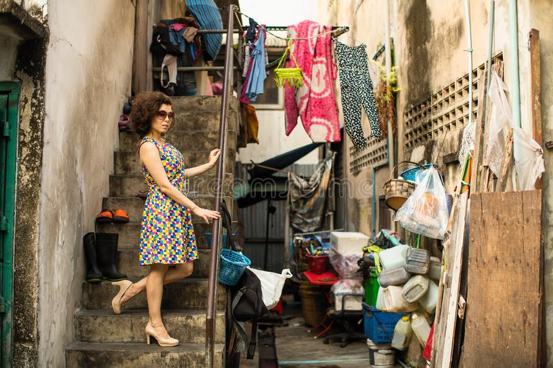 Asian woman stands in the slums of the street. Travel. Asian woman stands in the slums of the street royalty free stock image