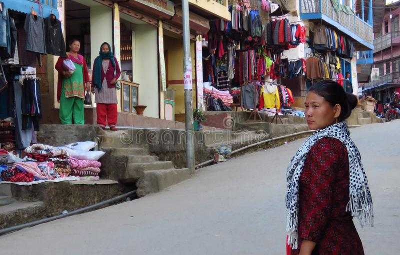 Asian woman on the streets of Khandbari going to the shop, Nepal. Khandbari, Sankhuwasabha District, Nepal - 11/15/2017: nepalese lady on the main shopping stock images