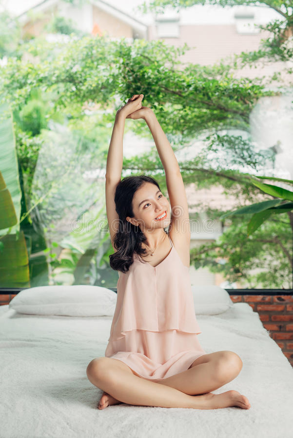 Asian woman stretching sitting on bed in the morning royalty free stock photo