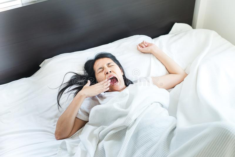 Asian woman stretching and yawning or gape feeling lazy on bed after wake up in the morning royalty free stock photos