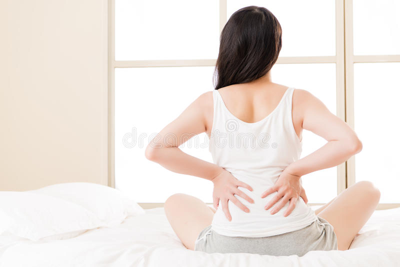 Asian woman suffers back pain backache, spinal lower problem royalty free stock photos