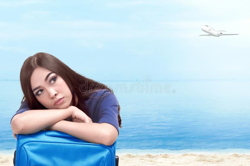 Asian woman with suitcase bag on the beach royalty free stock image