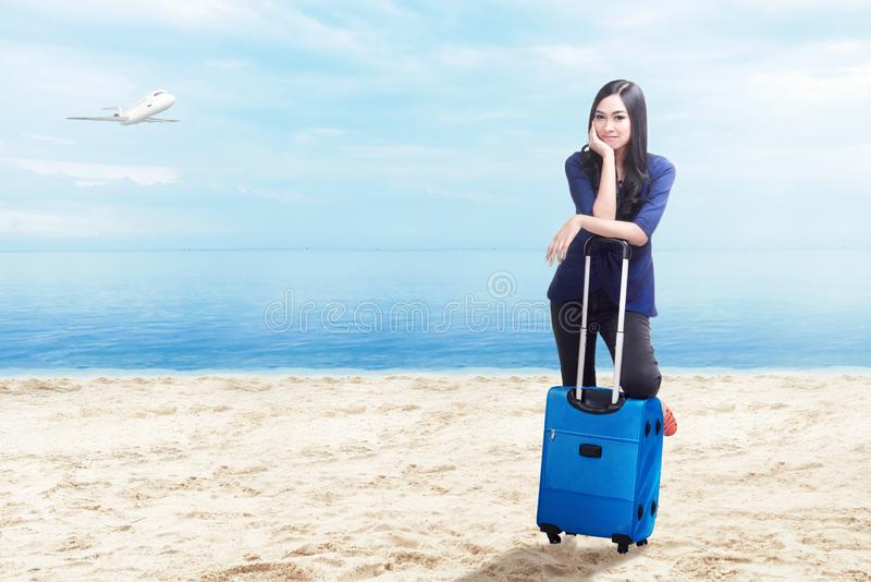 Asian woman with suitcase bag standing on the beach stock image