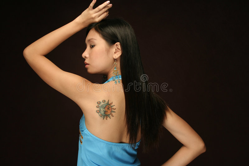 Asian Woman Sun and moon tattoo on shoulder. Sultry asian female model with sun and moon tattoo on her shoulder against dark brown background royalty free stock photo