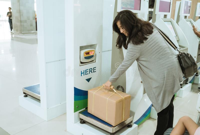 Asian woman take the cardboard on the luggage scale stock images