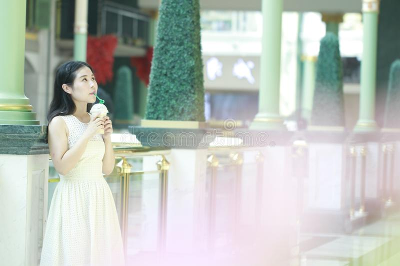 Asian Woman Take a takeout drink in hand. Standing in the corridor of the mall. Enjoy leisure time stock photos