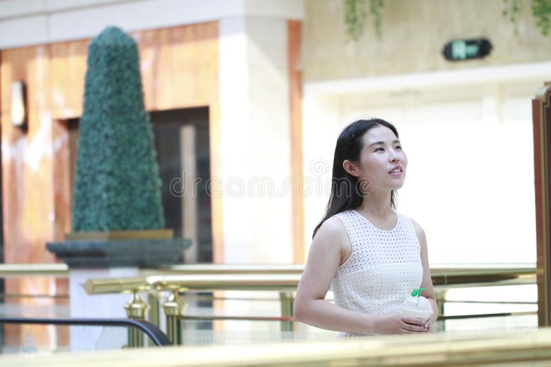 Asian Woman Take a takeout drink in hand. Standing in the corridor of the mall. Enjoy leisure time royalty free stock images
