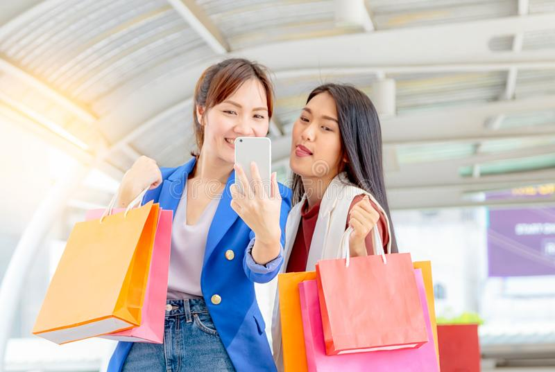 Asian woman taking selfie with smart phone in shoppi. Happy young Asian women taking selfie with smart phone in shopping mall stock photo