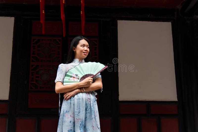 Asian woman in a temple holding a hand fan. Portrait stock photography