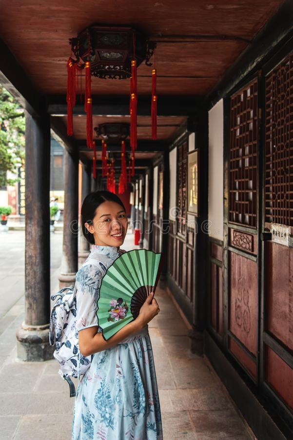 Asian woman in a temple holding a hand fan royalty free stock image