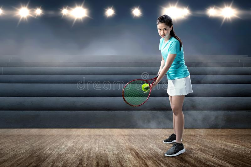 Asian woman with a tennis racket and ball in her hands ready in serve position royalty free stock images