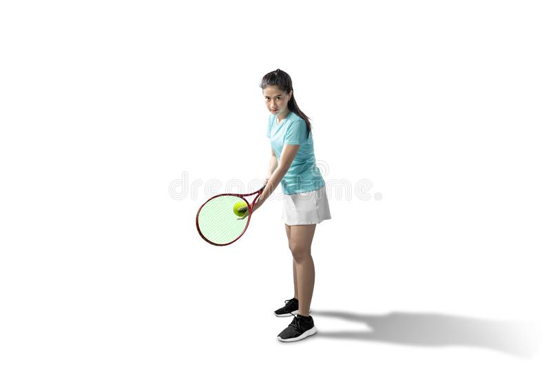 Asian woman with a tennis racket and ball in her hands ready in serve position royalty free stock photography