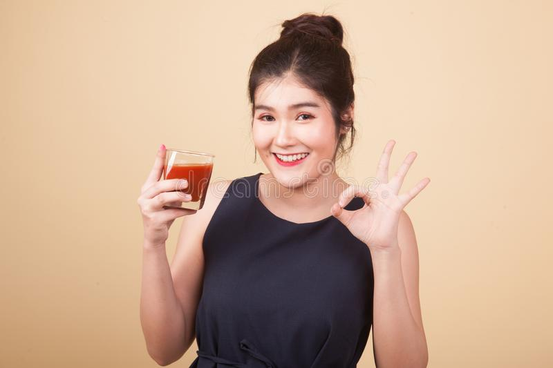 Asian woman thumbs down hate tomato juice. Young Asian woman thumbs down hate tomato juice on beige background royalty free stock images
