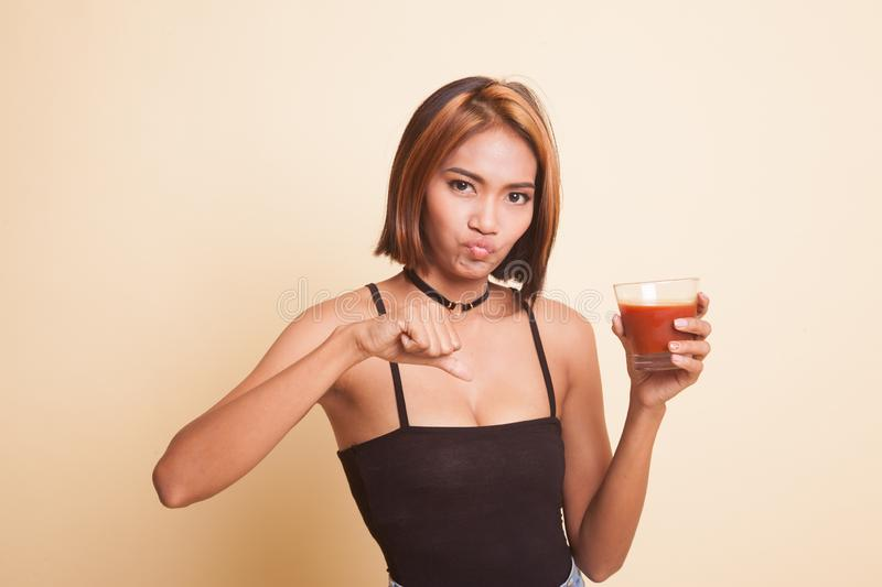 Asian woman thumbs down hate tomato juice. Young Asian woman thumbs down hate tomato juice on beige background royalty free stock photo