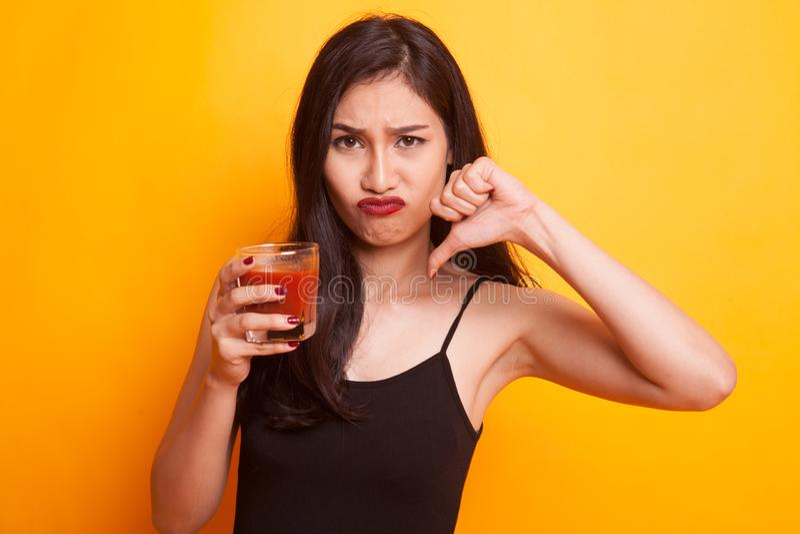 Asian Woman Thumbs Down Hate Tomato Juice. Stock Photo