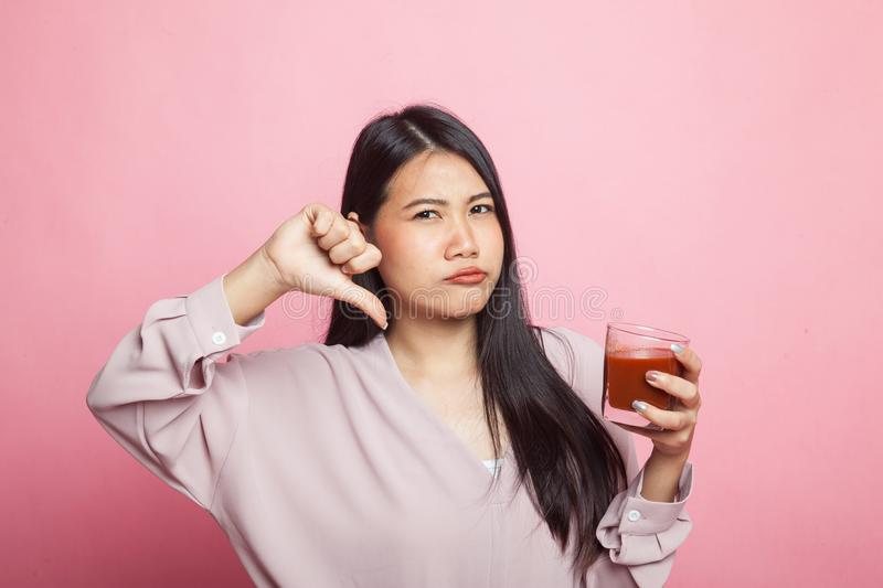 Asian woman thumbs down hate tomato juice. Young Asian woman thumbs down hate tomato juice on pink background stock images