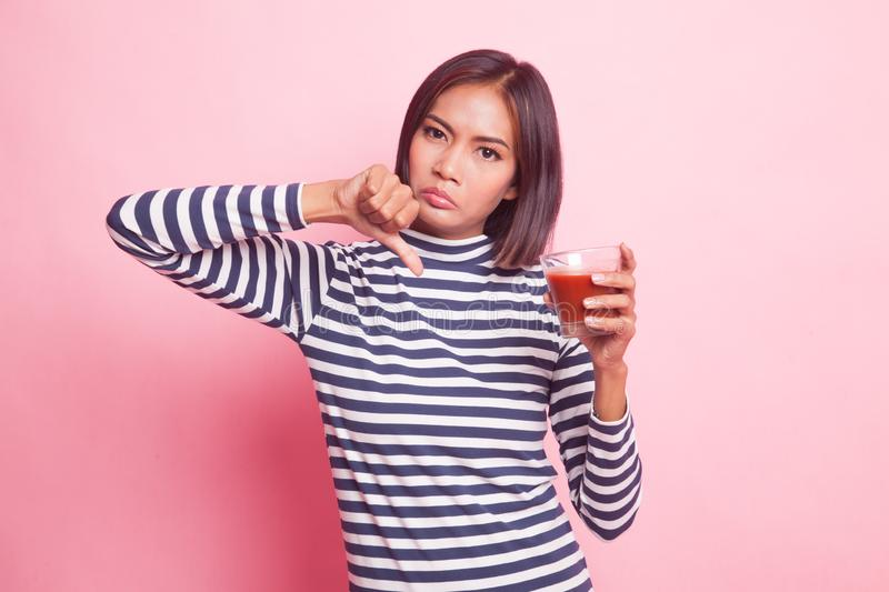 Asian woman thumbs down hate tomato juice. Young Asian woman thumbs down hate tomato juice on pink background stock photo