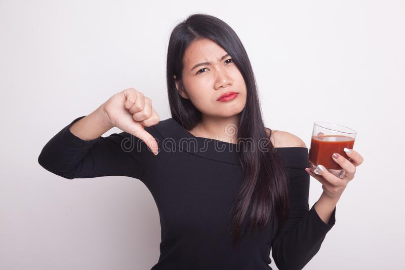 Asian woman thumbs down hate tomato juice. Young Asian woman thumbs down hate tomato juice on white background stock images