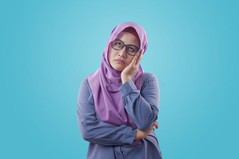 Asian Woman with Tired Sluggish Gesture. Portrait of young Asian muslim woman showing tired diizzy sluggish gesture, against blue background, arab, indonesian royalty free stock image