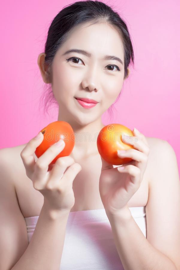 Asian woman with tomato concept. She smiling and holding tomato. Beauty face and natural makeup. Isolated over pink background. royalty free stock images