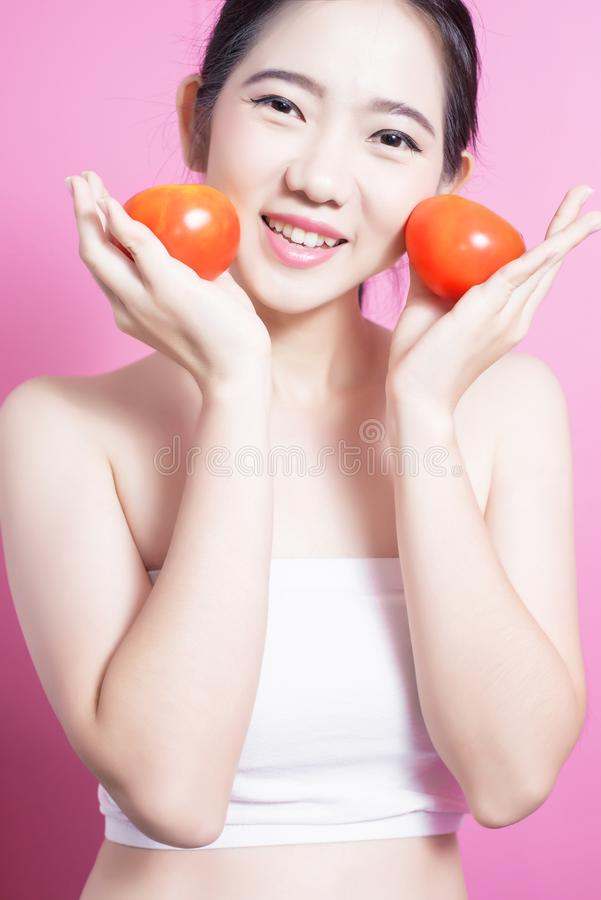 Asian woman with tomato concept. She smiling and holding tomato. Beauty face and natural makeup. Isolated over pink background. royalty free stock photo