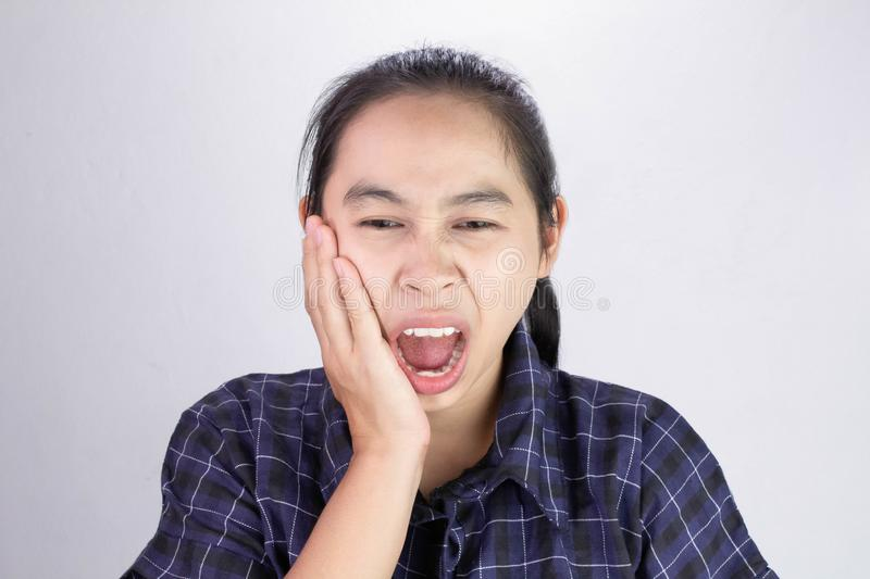 Asian woman touching cheek with hand because she is suffering of toothache. Dental care and health concept royalty free stock image