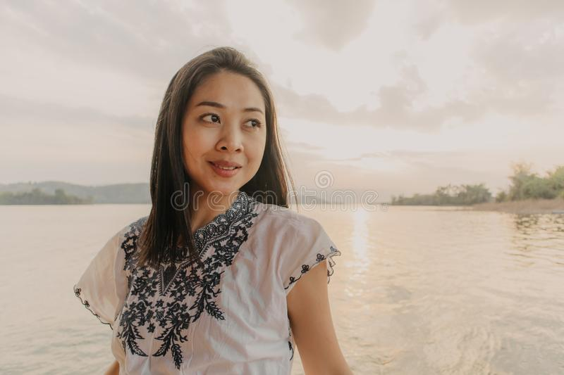 Woman tourist admire the beautiful nature of the lake with warm sunset sky stock photo