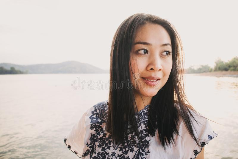 Woman tourist admire the beautiful nature of the lake with warm sunset sky stock photos