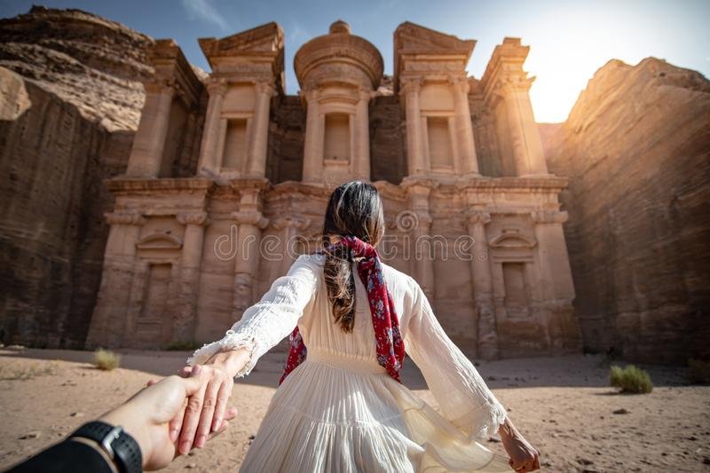 Asian woman tourist holding hand in Petra, Jordan. Asian woman tourist in white dress holding her couple hand at Ad Deir or El Deir, the monument carved out of royalty free stock images