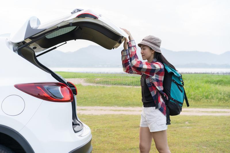 Asian woman travel camping on vacation. A girl open and close back door hatchback car white color on nature green view.  royalty free stock photos