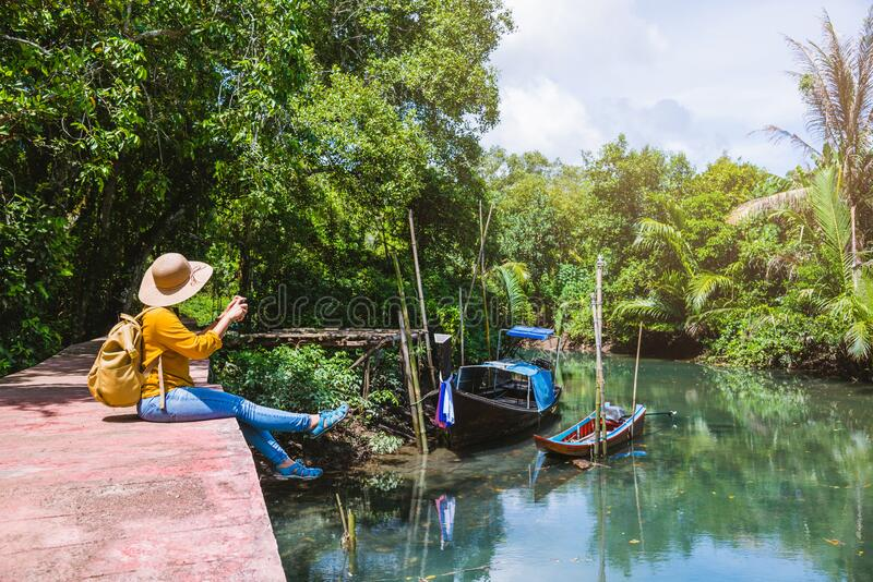 Asian woman travel nature. Travel relax.a boat photo. Sitting watching the beautiful nature at tha pom-klong-song-nam. Krabi, in stock photography
