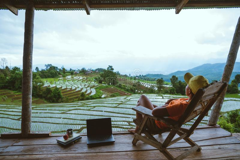 Asian woman travel nature. Relax read a book in the hammock. the balcony of the resort. View of the field on the Moutain in summer royalty free stock images