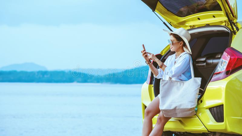 Asian woman travel nature. Travel relax. Sitting on the car at the beach. The girl travel nature travel in the holiday. summer royalty free stock photography