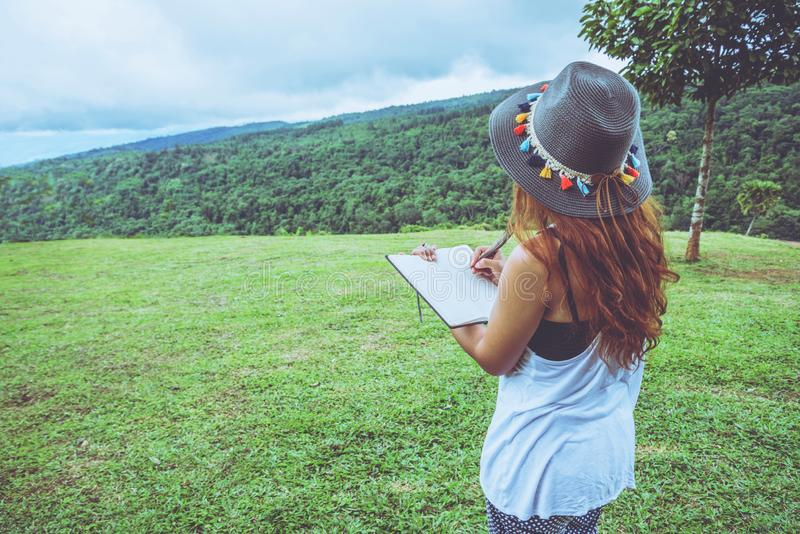 Asian woman travel nature. Travel relax. Study read a book. Nature Education Write a note At public park in summer. In Thailand stock photography