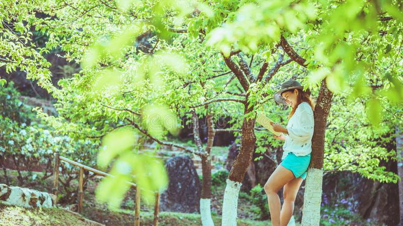 Asian woman travel nature. Travel relax. Reading book On the in the park. in summer. Education royalty free stock image