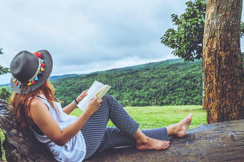 Asian woman travel nature. Travel relax. Study read a book. Nature Education. At public park in summer. Girl sitting reading, education stock images