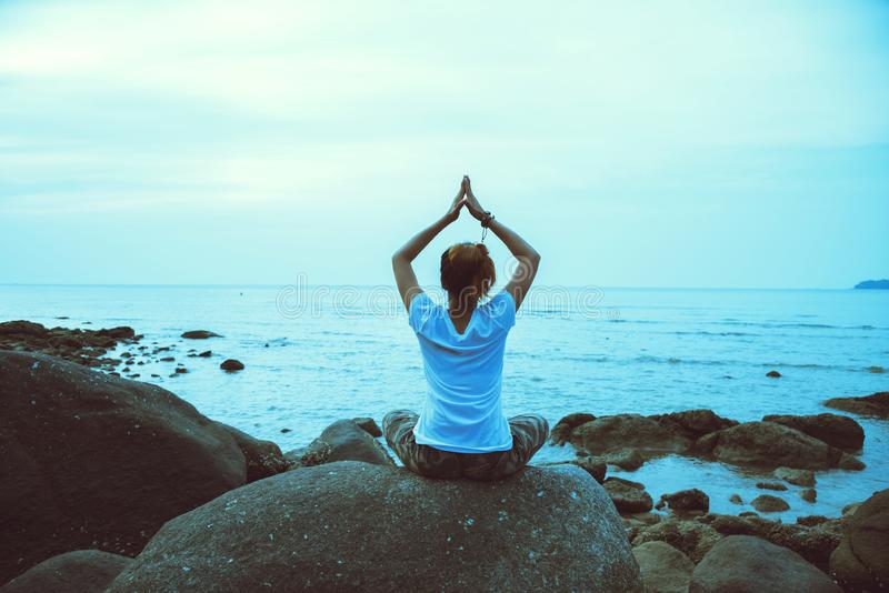 Asian woman travel relax in the holiday. Play if yoga. On the rocks by the sea.  royalty free stock photos