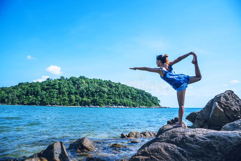Asian woman travel relax in the holiday. Play if yoga. On the rocks by the sea. Summer stock images