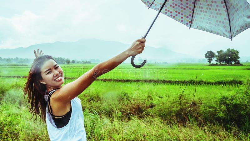 Asian women travel relax in the holiday. Women stand in rain umbrellas. On the meadow During the rainy season.Thailand. Asian woman travel relax in the holiday stock photos