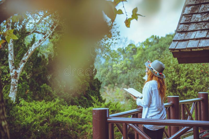 Asian woman travel relax. Natural park on the Moutain. Stand read a book on the balcony of the lodge stock photo