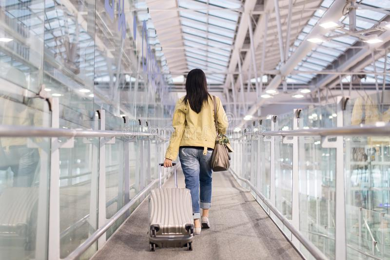 Asian woman traveler dragging carry on luggage suitcase at airport corridor walking to departure gates royalty free stock photography
