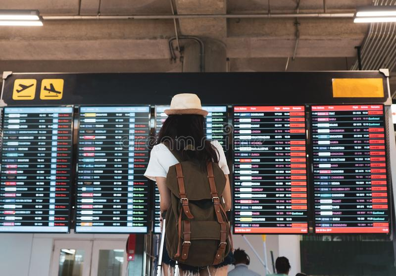 Asian woman traveler looking information board with carrying, suitcase. Luggage and passenger for tour travel booking ticket flight in airport international royalty free stock image