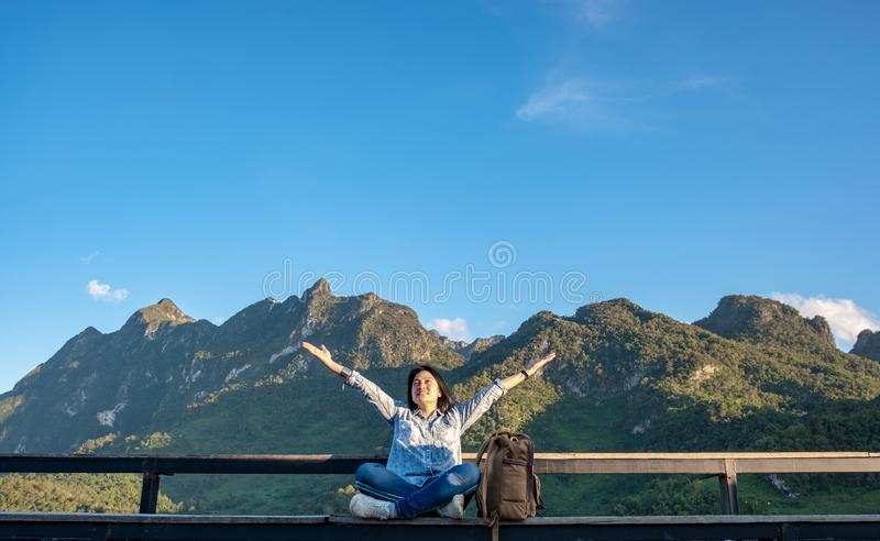 Asian woman traveler sitting and arms up in the air at view point terrace at landscape view of mountain with cloud and blue sky. In sunny day at forest royalty free stock photos