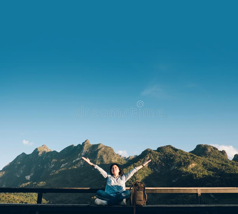 Asian woman traveler sitting and arms up in the air at view point terrace at landscape view of mountain with cloud and blue sky. In sunny day at forest stock image